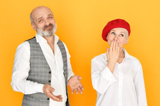 Attractive unshaven man with bald head having frustrated mournful expression, making helpless gesture, his beautiful stylish mature wife looking up in surprise, covering mouth with hand, gasping Free Photo