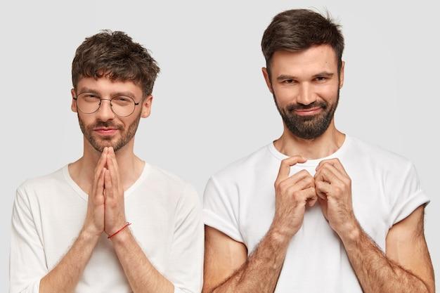 Attraenti due giovani uomini con la barba lunga hanno un aspetto intrigante, tengono le mani unite, vestiti con abiti casual, isolati su un muro bianco. hipster belli pongono al coperto Foto Gratuite