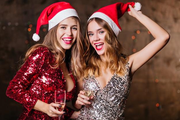 Привлекательные хорошо одетые женщины, наслаждающиеся рождеством вместе Бесплатные Фотографии