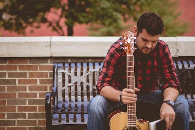 Maschio bianco attraente che si siede su una panchina che tiene la chitarra Foto Gratuite