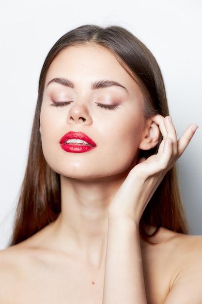 Привлекательная женщина с чистой кожей, голые плечи, закрытые глаза, очарование красных губ Premium Фотографии