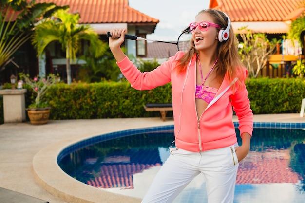 夏休みにヘッドフォンで音楽を聴いてサングラスをかけているカラフルなピンクのパーカーでプールでスポーツをしている魅力的な女性、テニス、スポーツスタイル 無料写真