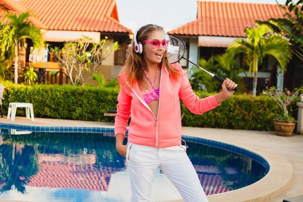 Donna attraente che fa sport in piscina in felpa con cappuccio rosa colorato che indossa occhiali da sole ascoltando musica in cuffia in vacanza estiva, giocare a tennis, stile sportivo Foto Gratuite