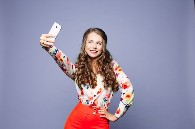 Attractive woman in floral shirt and red shorts taking self-portrait over violet background. Premium Photo