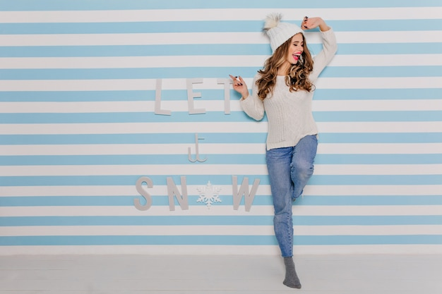 魅力的な女性は楽しんで笑います。白いセーターとワイドジーンズのポーズの女の子 無料写真