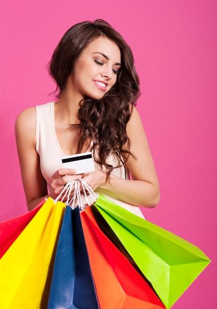 쇼핑백과 신용 카드를 들고 매력적인 여자 무료 사진
