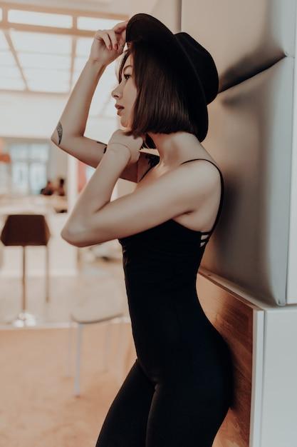 Привлекательная женщина в черном платье и шляпе, стоя возле стены в роскошной квартире Бесплатные Фотографии