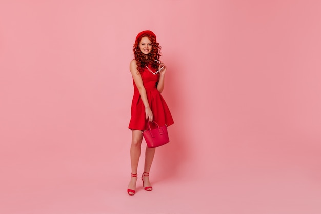 발 뒤꿈치에 매력적인 여자는 안경을 벗고 카메라에 보인다. 핑크 스튜디오에서 핸드백과 함께 포즈 빨간 드레스를 입은 곱슬 소녀. 무료 사진