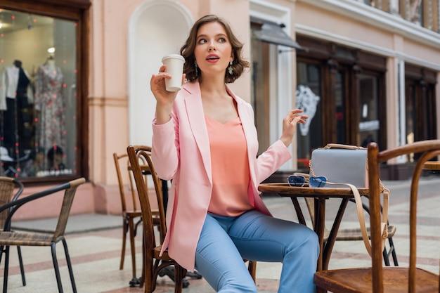 분홍색 재킷, 세련된 의류를 입고 테이블에 앉아 행복에 미소 짓는 낭만 분위기의 매력적인 여자, 카페에서 데이트하는 남자 친구를 기다리고, 카푸치노를 마시고, 얼굴 표현을 종료했습니다. 무료 사진