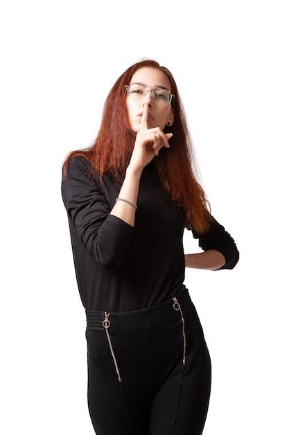 스타일링과 검은 Twater 재킷과 바지 침묵에서 그의 입에 손가락을 잡고 흰색 격리 된 배경에 카메라를보고 밝은 화장에 매력적인 여자. 여성 초상화 프리미엄 사진