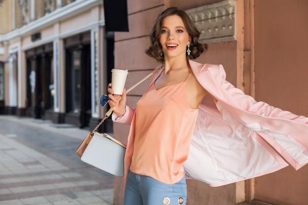 도시, 거리 패션, 봄 여름 트렌드, 행복한 분위기 미소, 분홍색 재킷과 블라우스 입고, 회전, 종료, 쇼핑 패셔니에서 걷는 세련된 복장에 매력적인 여자 무료 사진
