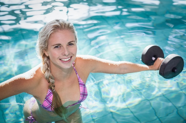 Attractive woman lifting dumbbells in the pool Premium Photo