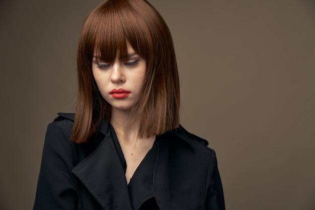 魅力的な女性の明るい肌の黒いコートベージュの背景 Premium写真