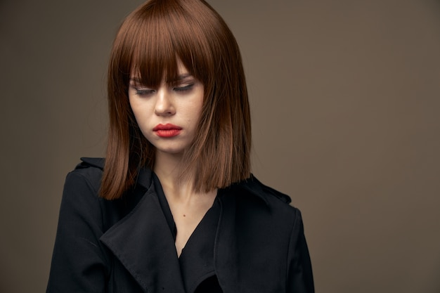 魅力的な女性の明るい肌の黒いコートベージュ Premium写真