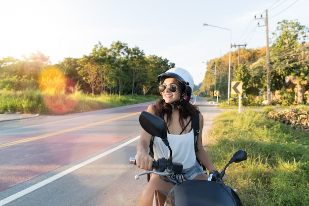 Attractive woman on motorcycle wear helemt on countryside road pretty woman motorcyclist travel on m Premium Photo