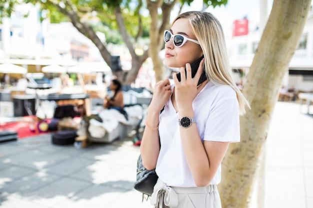 夏の屋外で電話で話している間ポーズをとる魅力的な女性 無料写真