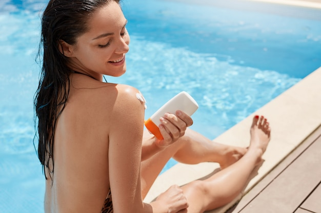 Attractive woman putting solar cream or sunblock on her armor shoulder, smiling lady dresses bikini by pool. beautiful young woman under sun on sunny summer day, relaxing at luxury spa resort. Premium Photo