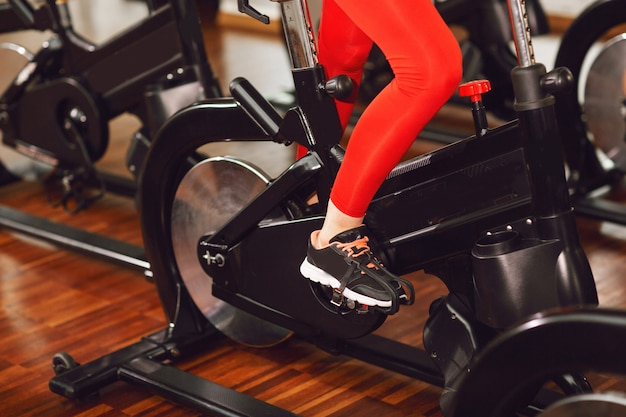 Attractive woman in a red sports suit in gym, riding on speed stationary bike. women's legs close up Premium Photo