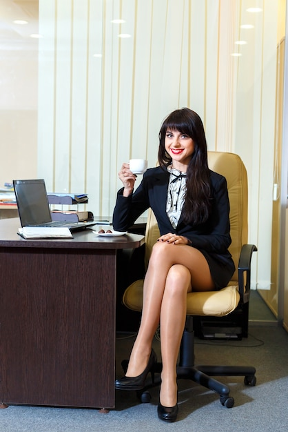 Attractive woman in a short skirt drinking coffee in the office Premium Photo