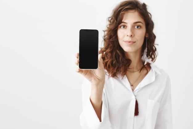 Привлекательная женщина показывает дисплей смартфона, рекламирует приложение Бесплатные Фотографии