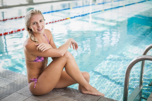 Attractive woman sitting on the edge of the pool Premium Photo