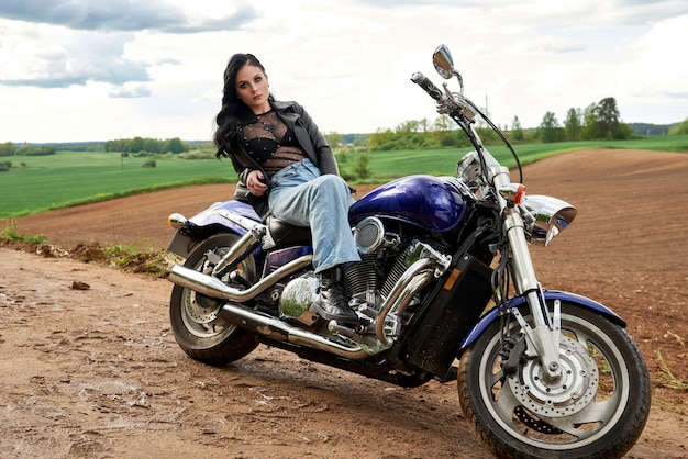 Attractive woman sitting on a motorcycle at sunset in a field. Premium Photo