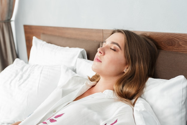 Attractive woman sleeping in bed in hotel room Premium Photo