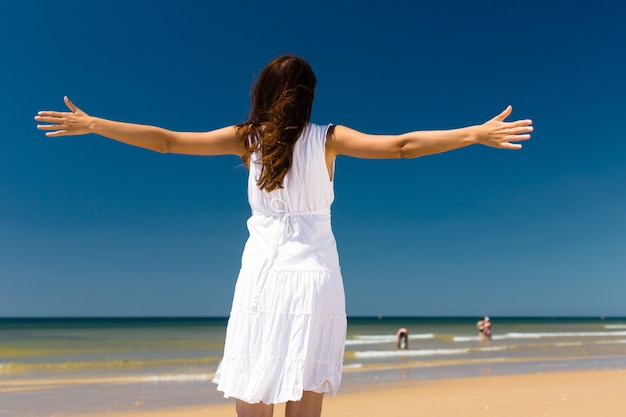 Attractive woman standing in the sun on beach Premium Photo