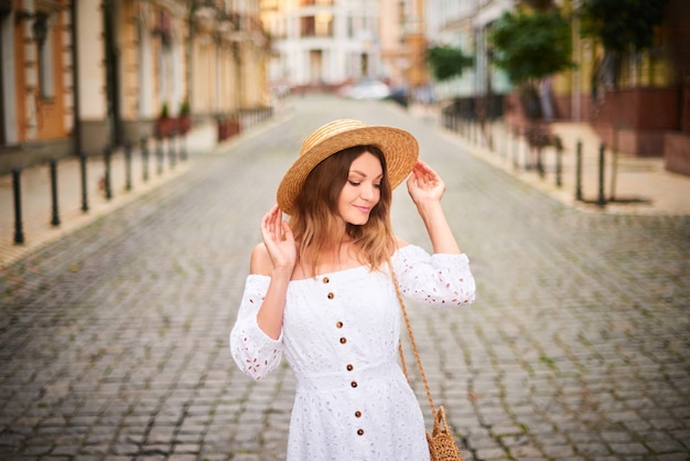 Attractive woman in straw hat and white sundress enjoying vacation Premium Photo