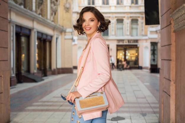 Donna attraente in abito elegante che cammina in città, moda di strada, tendenza primavera estate, umore sorridente felice, indossa giacca rosa e camicetta, gira intorno, è uscita, fashionista per lo shopping Foto Gratuite