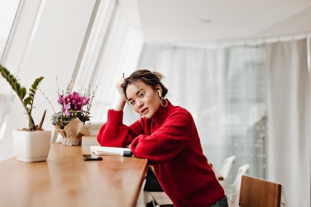 La donna attraente in vestito rosso alla moda si è appoggiata al tavolo Foto Gratuite