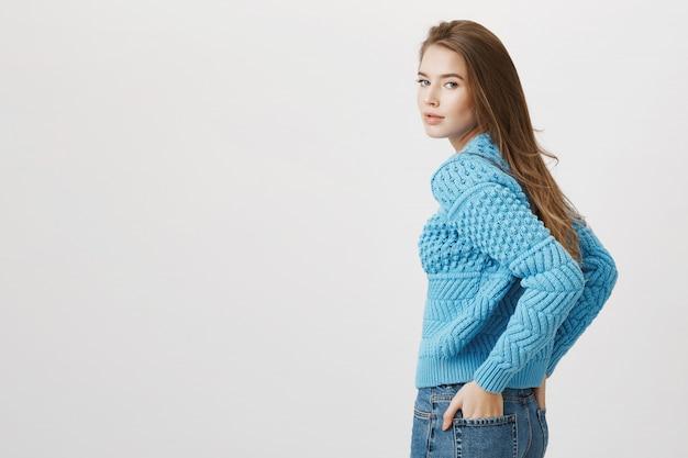 La donna attraente gira indietro alla macchina fotografica, tiene le mani nelle tasche dei jeans Foto Gratuite