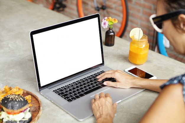 온라인 친구에게 문자 메시지를 보내는 동안 콘텐츠 복사 공간 화면이있는 일반 노트북에 메시지를 입력하거나 읽는 매력적인 여자 무료 사진
