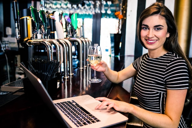 Attractive woman using laptop and having a glass of wine in a bar Premium Photo