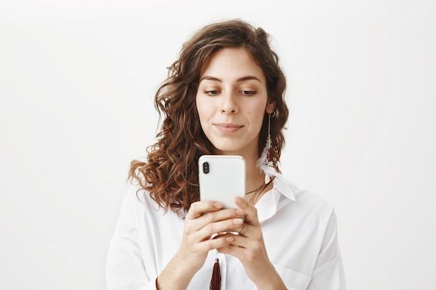 Donna attraente utilizzando il telefono cellulare, scarica l'applicazione Foto Gratuite