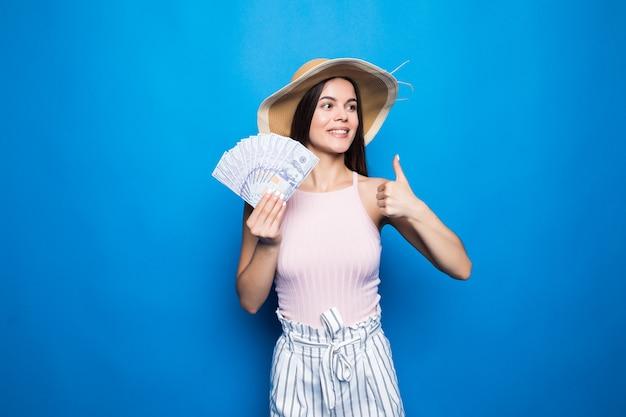 Donna attraente indossare in cappello di paglia che mostra banconote da 100 usd, pollice in su, isolato sopra la parete blu. Foto Gratuite