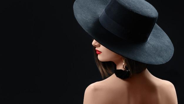Привлекательная женщина в шляпе позирует на черном фоне Premium Фотографии