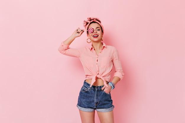 핑크 공간에 롤리팝 포즈 핀-업 셔츠와 머리띠를 입고 매력적인 여자. 무료 사진