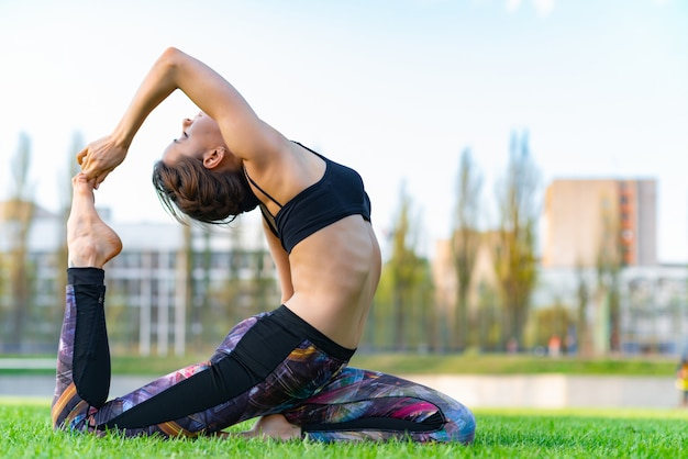 Attractive woman wearing sportswear doing yoga with deflection back Premium Photo
