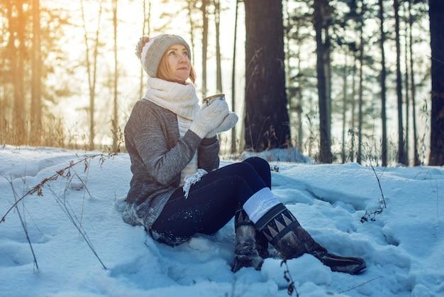 Attractive woman in winter drinking hot tea on sunlight Premium Photo