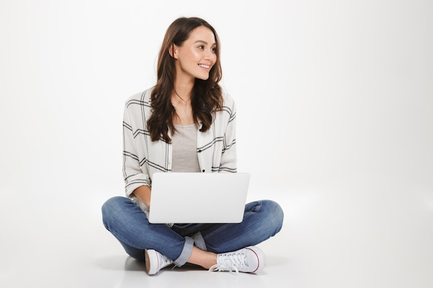Attractive woman with beautiful smile sitting in lotus pose on the floor using silver notebook and looking away, isolated over white wall Free Photo