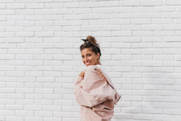 흰색 벽돌 벽에 포즈 핑크 데님 재킷에 검은 머리 밴드와 매력적인 여자 무료 사진