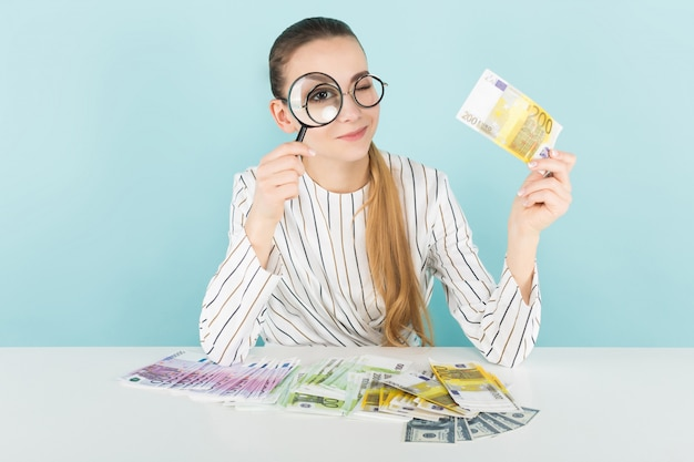 Attractive woman with cash and magnifying glass Premium Photo