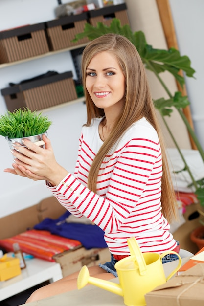 Attractive woman with grass with plant pot Free Photo