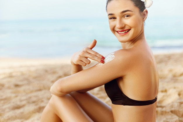 Attractive woman with healthy skin applying sunscreen to shoulder. Premium Photo