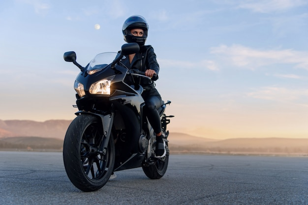 Attractive woman with long hair in black leather jacket and pants on outdoors parking with stylish sports motorcycle at sunset. Premium Photo