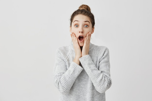 Attractive woman  with open mouth being shocked. female student grabbing face being astonished about exam result. education concept Free Photo