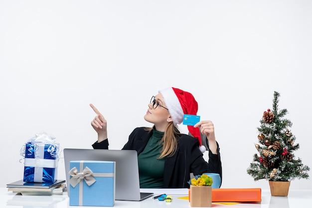 Привлекательная женщина в шляпе санта-клауса и очках сидит за столом, рождественский подарок и держит банковскую карту в офисе, кадры Бесплатные Фотографии