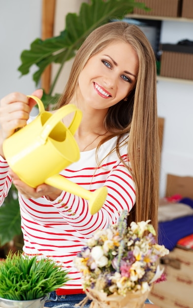 Attractive woman with watering can Free Photo