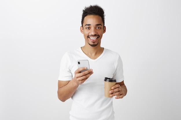 魅力的な若いアフリカ系アメリカ人の男は満足している、携帯電話を押しながらテイクアウトのコーヒーを飲む 無料写真